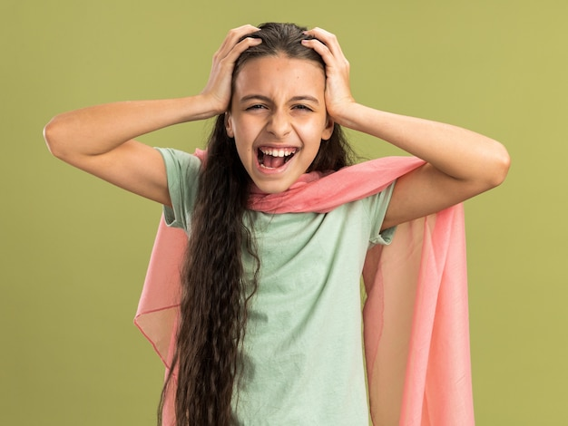 Stressed teenage girl wearing shawl keeping hands on head looking at camera isolated on olive green wall