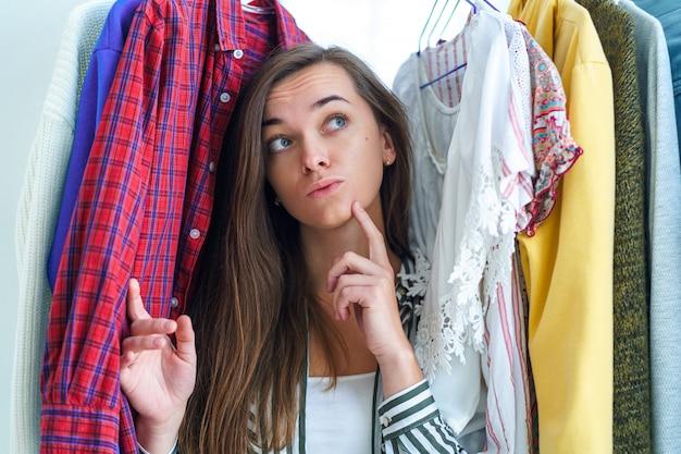 ハンガーに洋服だらけのワードローブラック近くに立っている女性の思考を強調