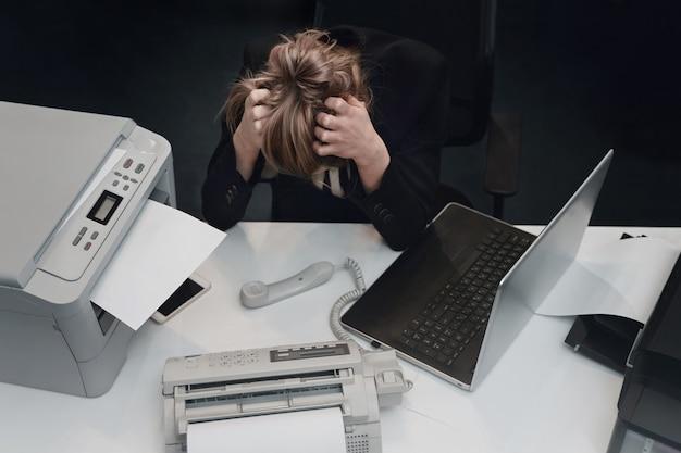 ストレスで疲れた実業家は、ノートパソコンを持ってオフィスの机に座って疲れ果てている
