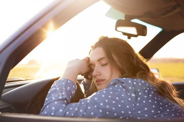 Stressed or tired girl in car lying with closed eyes on steering wheel, stops auto on side of road, spends long hours on her way
