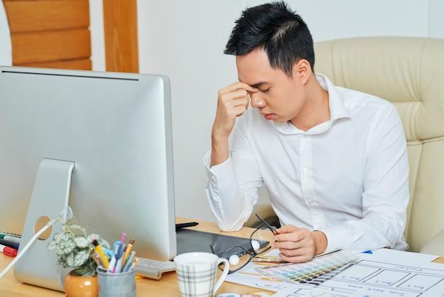 ストレスのたまった若いグラフィックデザイナーが眼鏡を外し、鼻の橋をこすります
