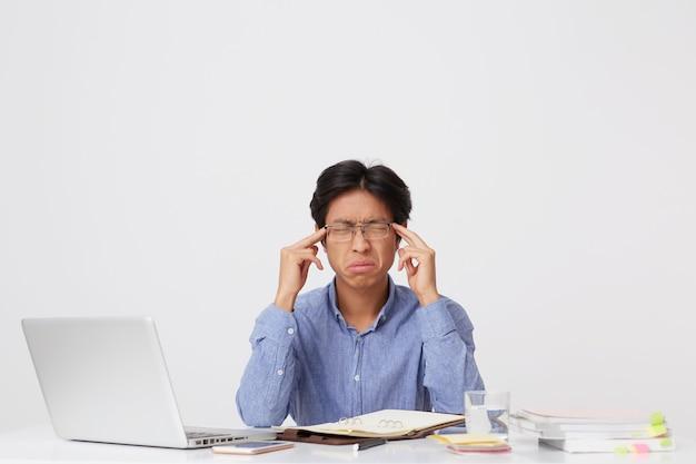 目を閉じてこめかみに触れて眼鏡をかけた不幸なアジアの若いビジネスマンを強調し、白い壁の上のテーブルでラップトップで圧力を感じます