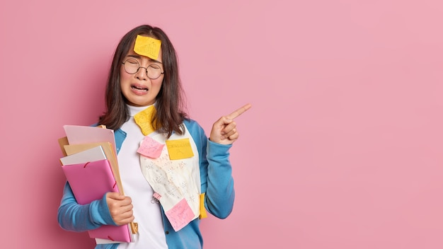 Stressed unhappy female student cries from desprair being fed up of exam preparation points away on blank space overloaded with papers has to remember much information.