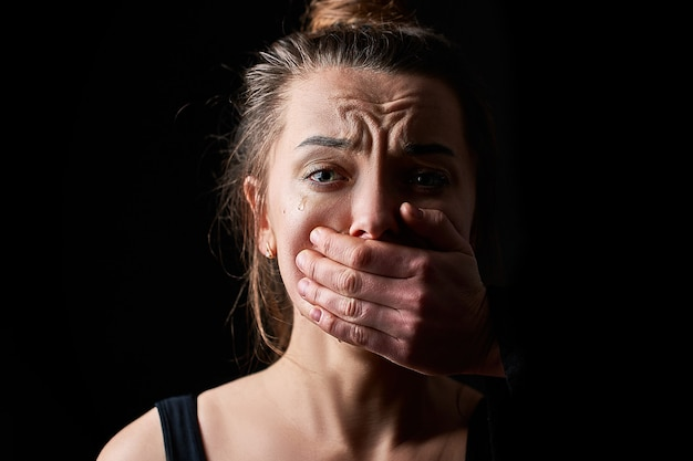 Stressed unhappy scared crying woman victim in fear with closed mouth on a dark black