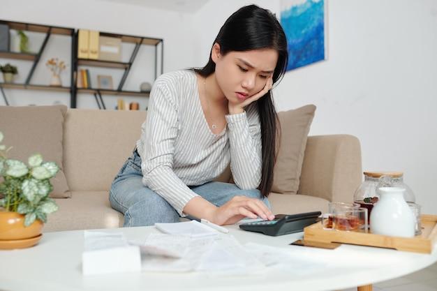毎月の税金、銀行口座の残高、クレジットカードの支払い請求書を計算する不幸な若いベトナム人女性を強調