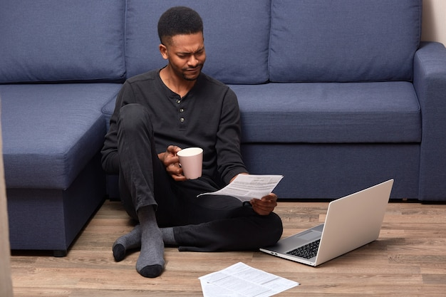 Stressed upset man sitting on floor holding rose cup with drink and document in both hands, reading attentively, using his laptop