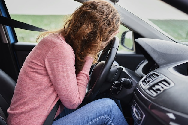 Stressed woman covering face with hands in car. driver panic concept