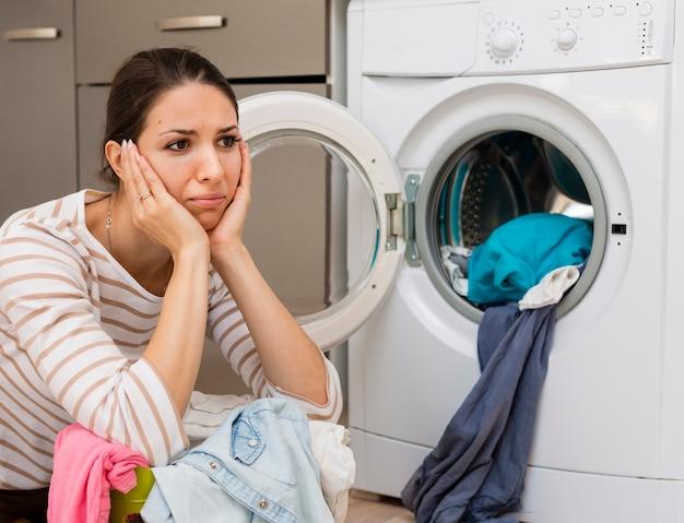 Stressed woman doing laundry medium shot