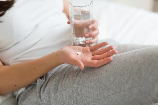 ストレスの多い女性が自宅のベッドで錠剤やコップ一杯の水で薬を飲む