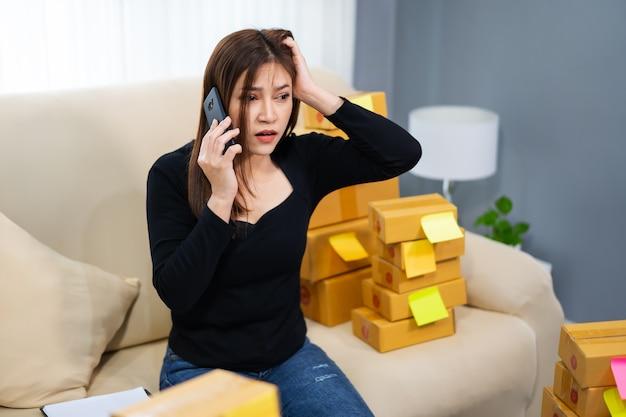 ストレスの多い女性起業家がスマートフォンで問題を話し、ホームオフィスでオンラインで製品を販売する