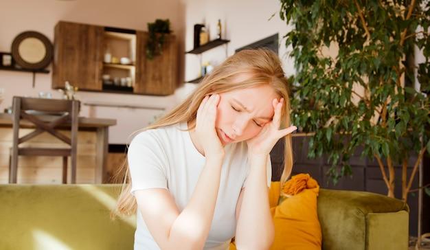 ストレスのたまった女性はひどい激しい頭痛、疲れた動揺した女性の痛みを感じます。片頭痛の概念。