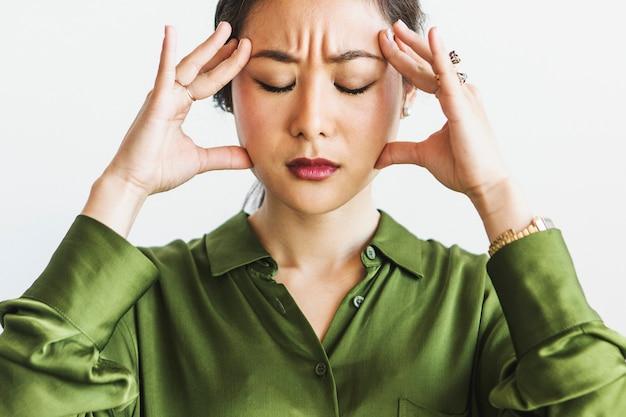 彼女の額を保持しているストレスの多い女性