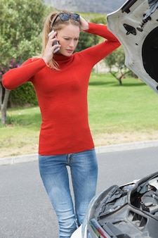 Stressed woman looking at engine Premium Photo