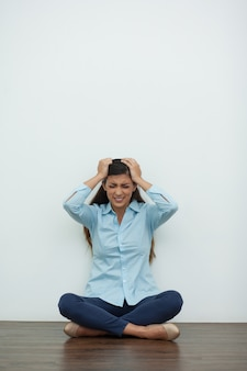 Stressed woman sitting on floor and clutching head