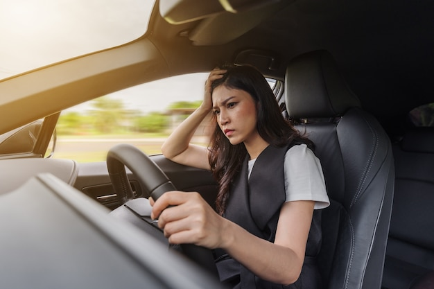 Stressed woman sitting inside a car