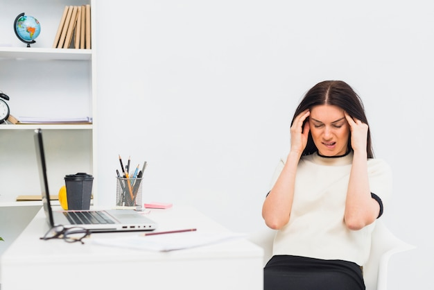 Stressed woman sitting at table in office