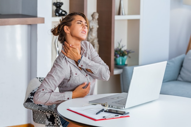 Stressed woman suffering from back pain after working on pc