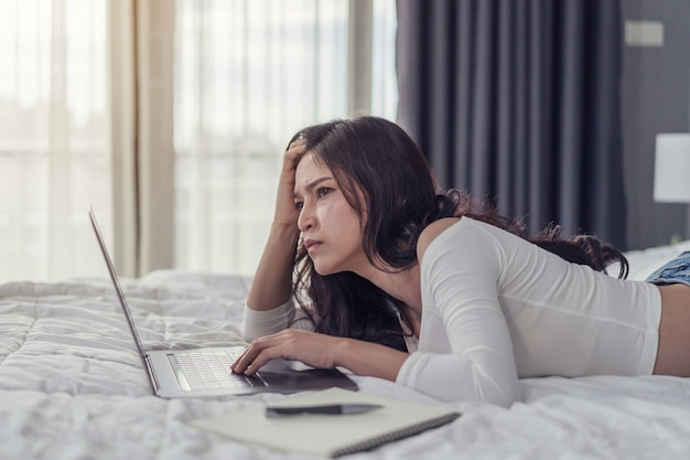 Stressed woman using laptop computer on bed