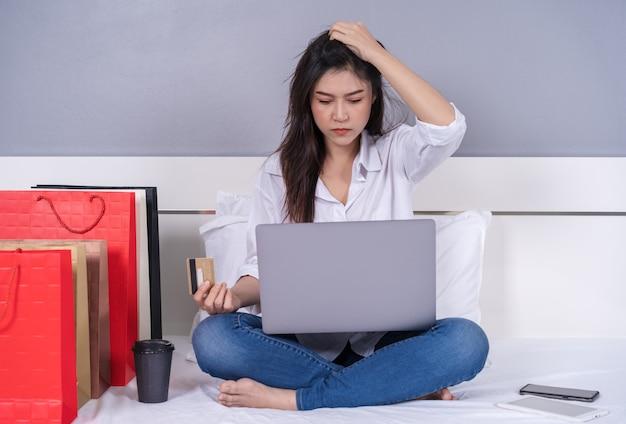 ベッドでオンラインショッピングのためにラップトップを使用し、ブロックされたクレジットカードに問題があると女性を強調した