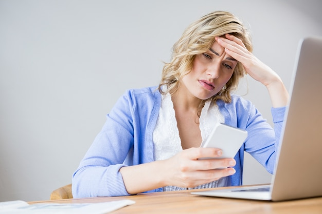 Stressed woman using mobile phone