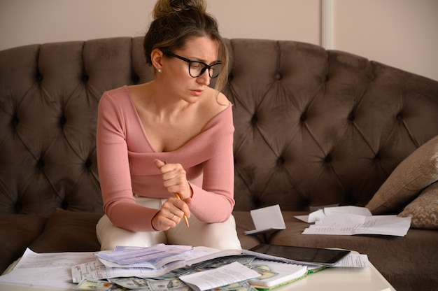 Stressed woman wearing black glasses looking over bills