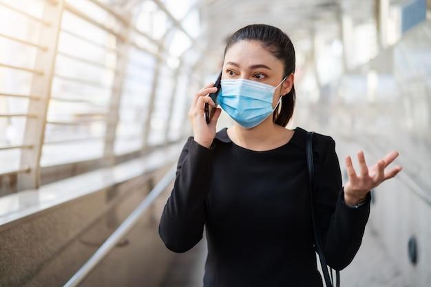Подчеркнула женщина в медицинской маске и разговаривает по мобильному телефону