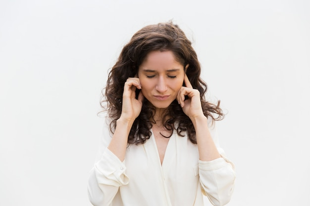 Stressed woman with closed eyes plugging ears with fingers