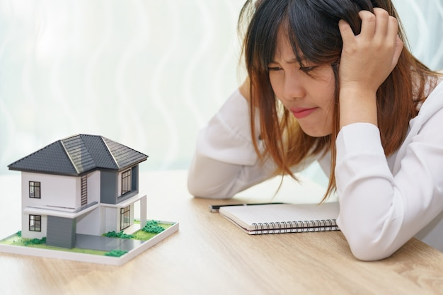Stressed woman with running out of money in piggy bank and her house