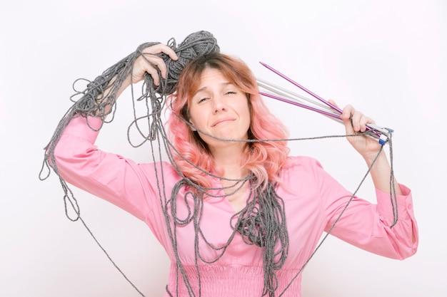 ウールと編み針が体に絡まったストレスの多い女性