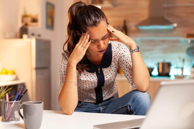 時間外労働をしているストレスのたまった女性は、夜遅くにコンピューターを使った後、目の倦怠感を感じます。深夜に最新のテクノロジーを使用して、仕事、ビジネス、忙しい、キャリア、ネットワーク、ライフスタイルのために残業している従業員。