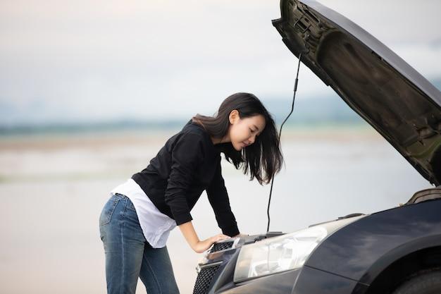 Подчеркнутые женщины после аварии автомобиля с красным треугольником автомобиля на дороге