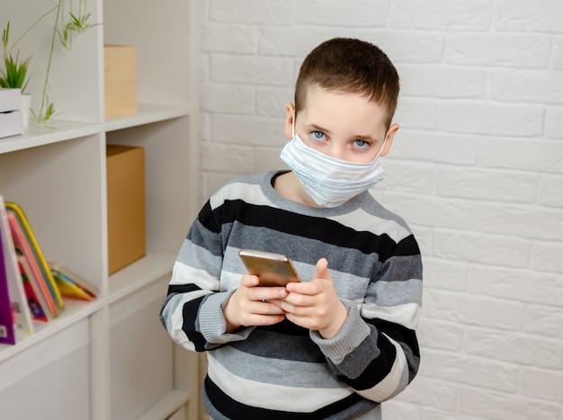 의료 얼굴 마스크를 쓰고 걱정되는 아이 소년을 강조하고 먼지의 양을 확인하십시오.