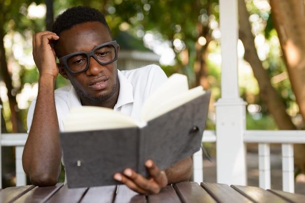 Подчеркнул молодой африканец как студент, читающий книгу и почесывающий голову в парке