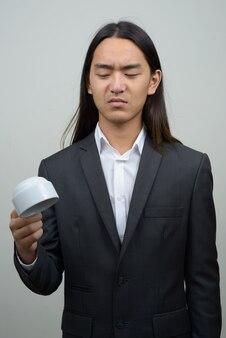 거꾸로 커피 컵을 들고 긴 머리를 가진 젊은 아시아 사업가 강조