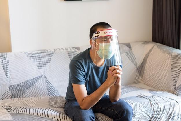 Подчеркнул молодой азиатский мужчина в маске и маске, молящийся во время просмотра телевизора дома в карантине