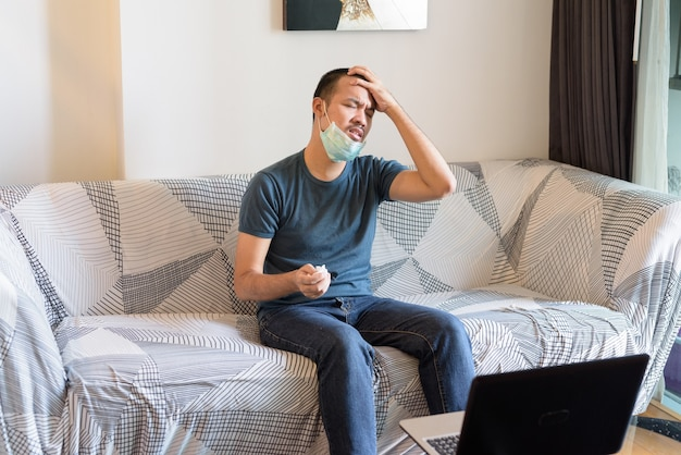 Stressed young asian man with mask having headache at home under quarantine