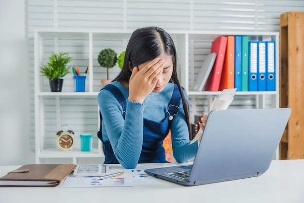 Stressed young asian woman administrative work holding bills after shopping online in special lower price day and discount coupon