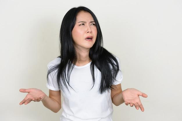 Подчеркнутая молодая азиатская женщина пожимает плечами и выглядит смущенной
