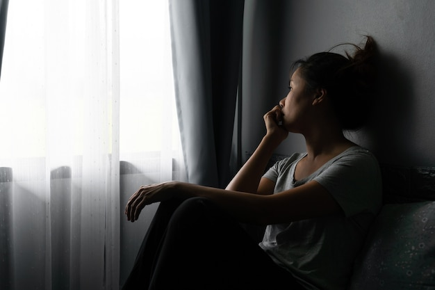 Stressed young asian woman suffering on depression and sitting alone on bed in dark room at home.