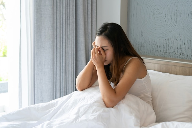Stressed young asian woman suffering on depression and sitting alone in bedroom at home. sad, unhappy, disappointed concept