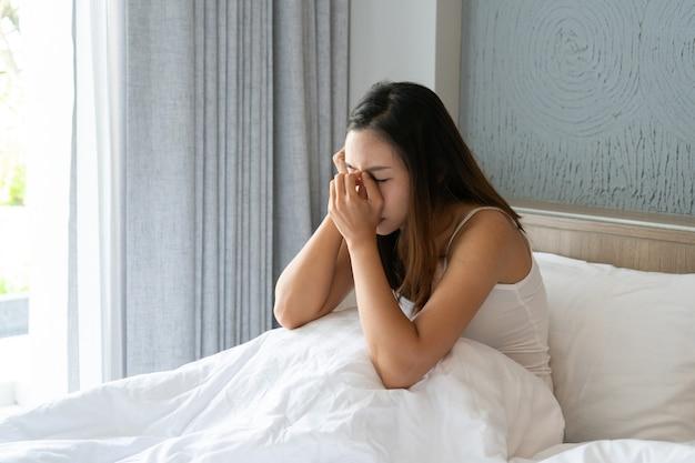 うつ病に苦しんでいる若いアジアの女性を強調し、自宅の寝室に一人で座っています。悲しい、不幸な、失望した概念