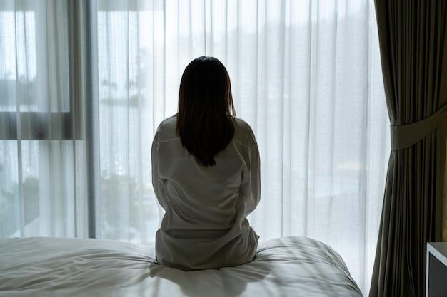 うつ病に苦しんでいて、自宅の暗い寝室に一人で座っている若いアジアの女性を強調しました。