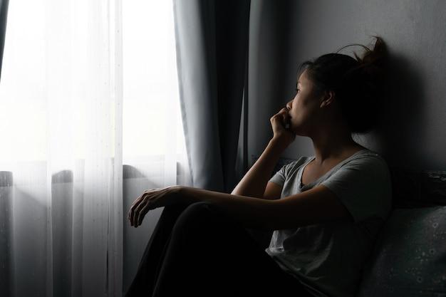 うつ病に苦しんでいる若いアジアの女性を強調し、自宅の暗い部屋のベッドに一人で座っています。