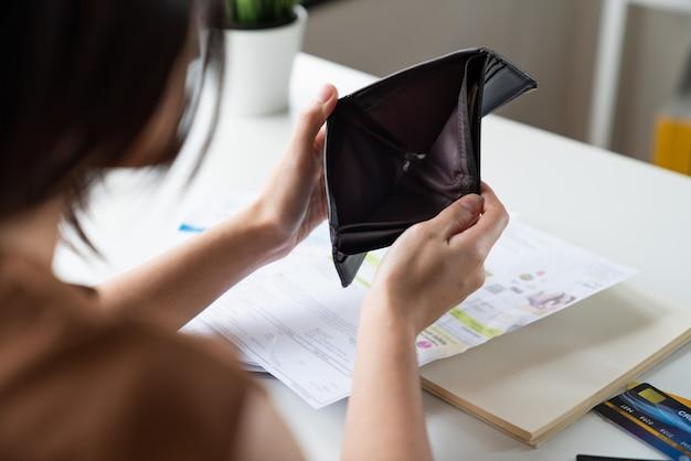 アジアの若い女性は、クレジットカードの請求書の借金を支払うお金がない開いた財布に座っている問題を抱えていると強調しました。