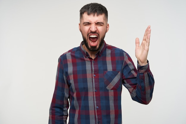 Stressed young attractive bearded brunette male with short haircut keeping his eyes closed while screaming angrily with raised hand, standing over white wall