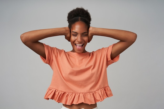 Stressed young attractive curly brunettened lady closing her ears and screaming with closed eyes, standing over grey wall in pink blouse
