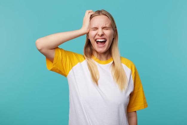 Sottolineato giovane attraente dai capelli lunghi femmina bionda tenendo la mano alzata sulla sua testa e gridando con gli occhi chiusi, in piedi su sfondo blu in t-shirt bianca e gialla