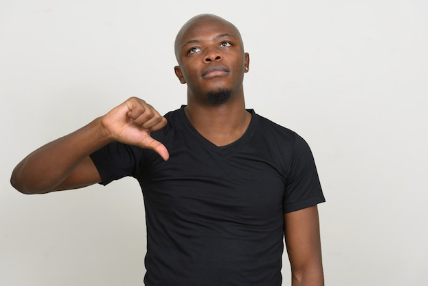 Stressed young bald african man giving thumbs down