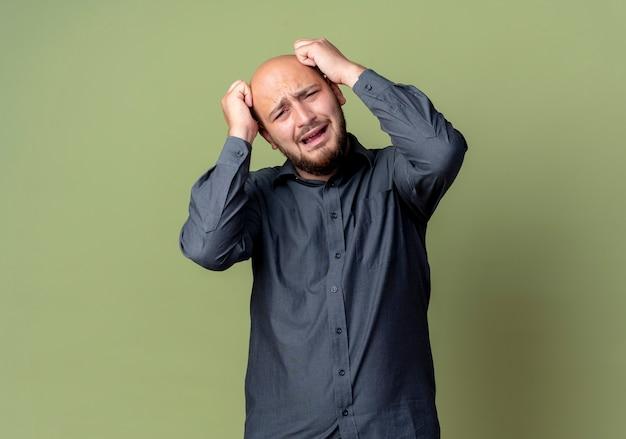 올리브 녹색 벽에 고립 된 머리에 손을 댔을 젊은 대머리 콜센터 남자를 강조