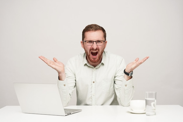 Stressed young bearded fair-haired male in glasses raising emotionally his palms while screaming with wide mouth opened, isolated over white background